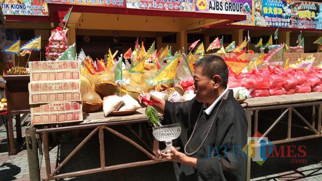 tokoh agama sedang memberkati sembako yang akan dibagikan kepada warga (foto : Joko Pramono/Jatim Times)