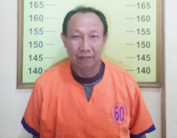 Aji Siswanto, pelaku penganiayaan Ibu RT. Kini meringkup di sel rutan Polsek Kota Banyuwangi