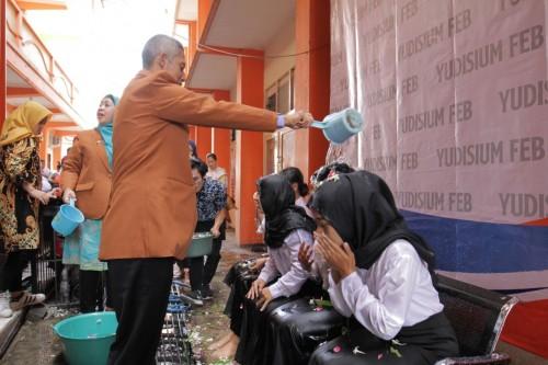 Dekan Fakultas Ekonomi dan Bisnis Unikama, Drs. Sulistyo, M.Ak mbk saat menyiramkan air bunga kepada mahasiswa dalam prosesi yudisium (foto: FEB Unikama for MalangTIMES)