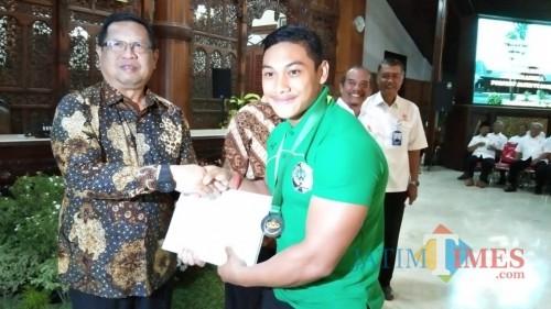 Maryoto Birowo saat berikan bonus bagi atlet angkat berat asal Tulungagng yang meraih medali dalam Porprov VI (foto : Joko Pramono/Jatim Times)