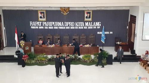 Ketua DPRD Kota Malang periode 2014-2019, Bambang Heri Susanto (kanan) saat menyerahkan palu sidang kepada Ketua Sementara DPRD Kota Malang, I Made Rian DK (kiri) (Pipit Anggraeni/MalangTIMES).