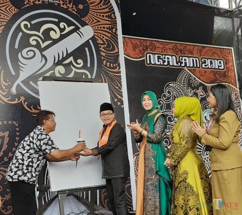 Wali Kota Malang Sutiaji (berkopyah) saat membuka Festival Batik Ngalam 2019 dengan penggoresan cat air (Arifina Cahyanti Firdausi/MalangTIMES)