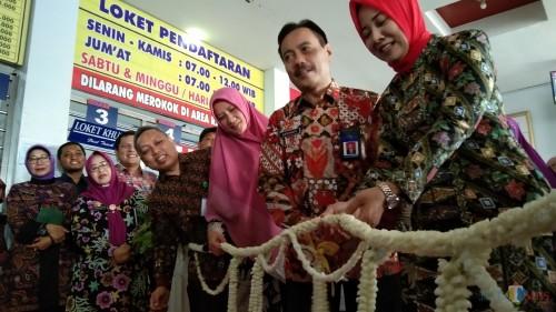 Supriyanto (batik merah) saat memotong untaian melati menandakan peresmian layanan Poetri dan Si Tole (foto : Joko Pramono/Jatim Times)