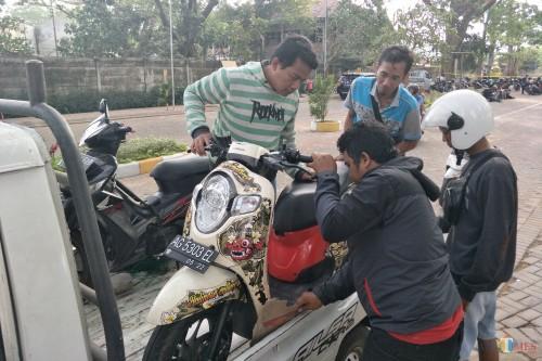 M Taufikul Hakim Persik Mania warga Pagu, Menang, Kabupaten Kediri ketika mengambil motornya yang tertahan di parkiran taman tirtoyoso. (Foto: Bambang Setioko/JatimTIMES)