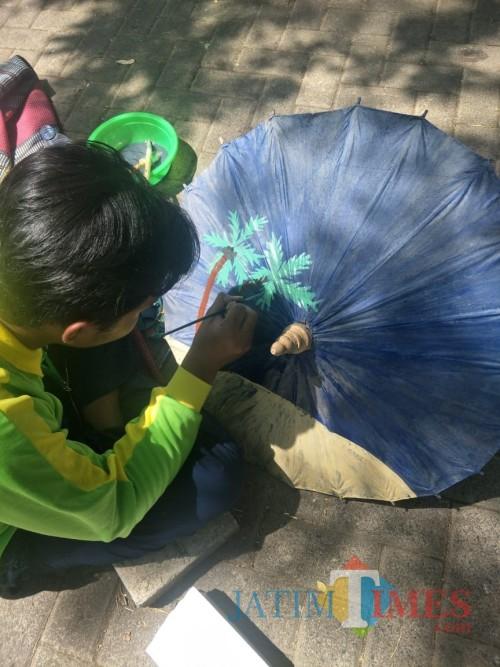 Asyiknya para pelajar mewarnai payung kertas dalam lomba yang digelar Dinas Pendidikan Kabupaten Malang di expo pembangunan (dd Nana)