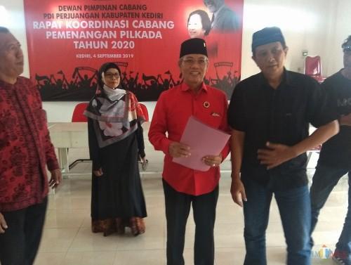 Wabup Kediri Masykuri ikhsan (tengah) saat mengambil formulir pendaftaran di Kantor PDIP Kabupaten Kediri. (eko Arif s /JatimTimes)