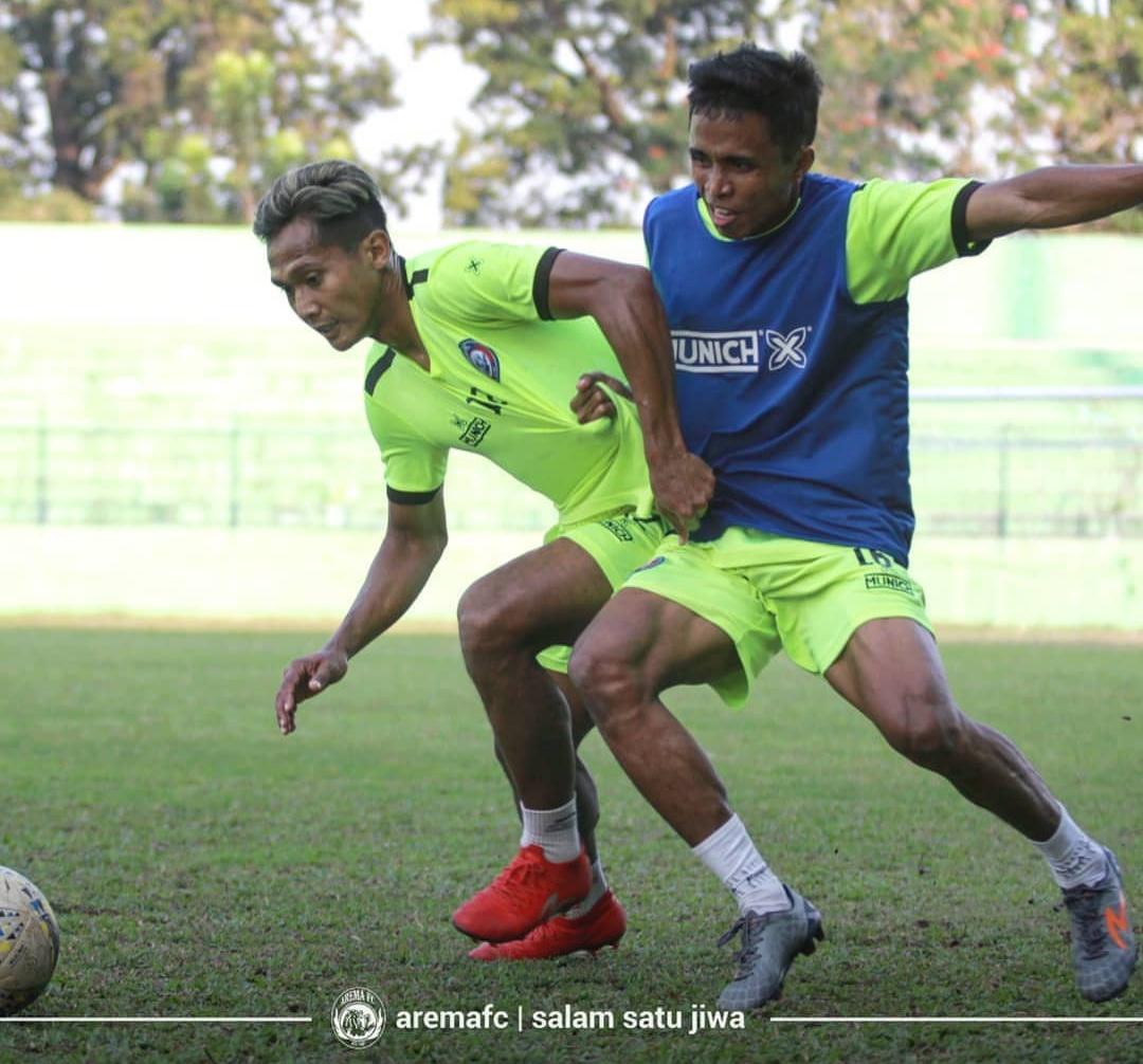 Ridwan Tawainella (kanan) saat berebut bola dengan Hendro Siswanto (official Arema FC)