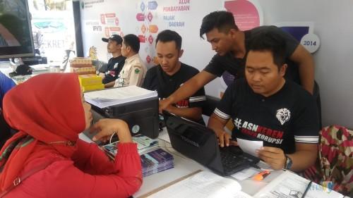 Petugas BP2D Kota Malang tengah melayani wajib pajak yang mengurus administrasi perpajakannya. (Foto: Nurlayla Ratri/MalangTIMES)