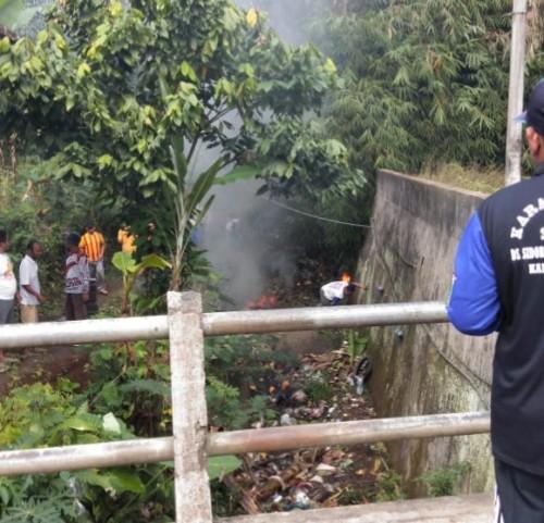 warga bersama KKN Unikama saat membersihkan dan membakar sampah di bawah jembatan yang dialiri Sungai Jagalan (Unikama for MalangTIMES)