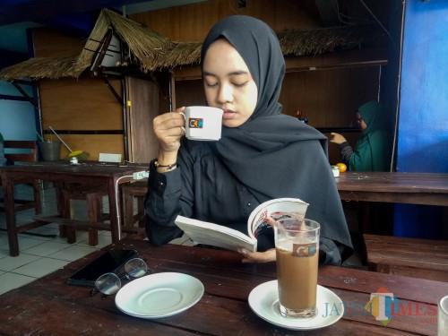 Sisca, salah satu pengunjung Coffee Times yang mencicipi kopi luwak Bromo Coffee Times. (Foto: Imarotul Izzah/MalangTIMES)