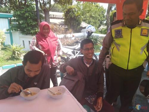 Kanit Turjawli Satlantas Polres Jombang, Iptu Mulyani terlihat ngobrol dengan pelanggar yang sedang menikmati bubur yang disediakan oleh pihak Satlantas. (Foto : Adi Rosul / JombangTIMES)
