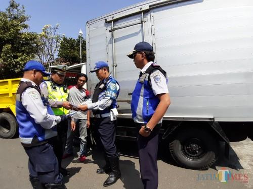 Petugas saat memeriksa kelengkapan surat-surat kendaraan dalam operasi gabungan (Arifina Cahyanti Firdausi/MalangTIMES)