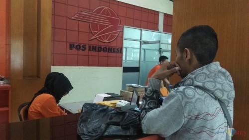 Warga tengah mengirimkan paket di Kator Pos Malang. (Foto: Nurlayla Ratri/MalangTIMES)