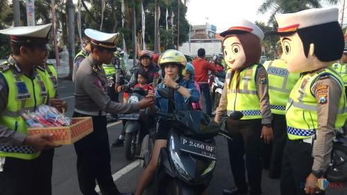 Petugas memberikan bunga dan cokelat pada salah seorang pengendara