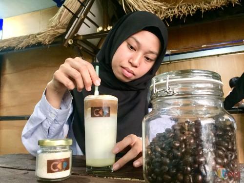 Salah satu pengunjung saat mencoba menu baru es susu kopi didi Terminal Kopi Malang, Pasar Terpadu Dinoyo, Kota Malang. (Foto: Irsya Richa/MalangTIMES)