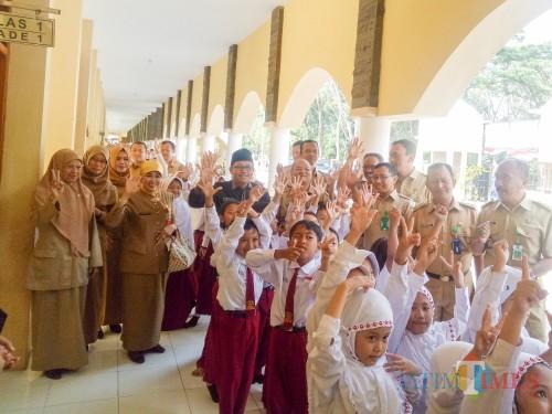 Kepala Dinas Pendidikan Kota Malang, Dra Zubaidah MM, dan Wali Kota Malang, Sutiaji, berfoto bersama siswa-siswi saat melakukan monitoring pelaksanaan Penguatan Pendidikan Karakter (PPK). (Foto: Imarorul Izzah/MalangTIMES)