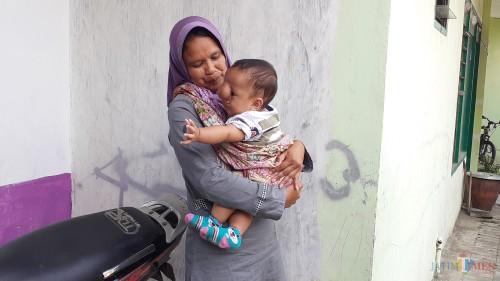 Arsa Adi Pratama, bayi 10 bulan yang mengidap meningokel, saat digendong sang ibundanya, Wiwin. (Pipit Anggraeni/MalangTIMES).