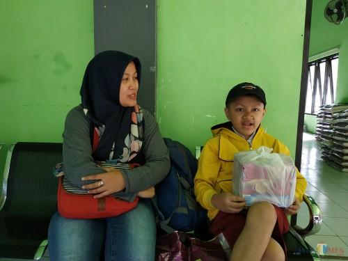Kevin Rivelino Putra (kanan) bersama ibundanya usai menerima bantuan sosial dari Dinsos Kota Malang (Hendra Saputra)