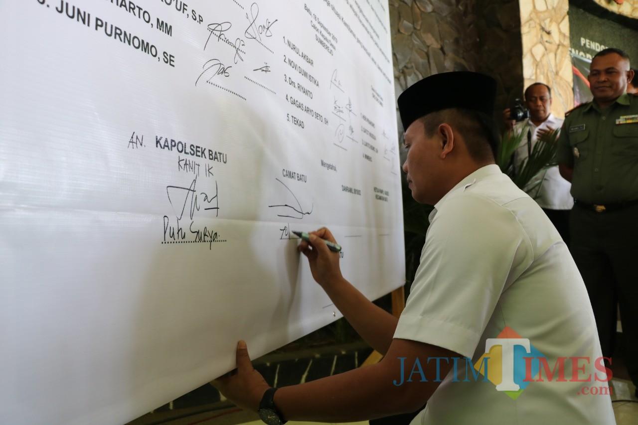 Camat Batu Yopi Supriadi saat menandatangani deklarasi damai di Pendopo Senopati Praja, Kecamatan Batu, Rabu (18/9/2019).