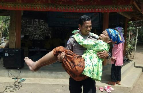 Nenek Misnah digendong Polisi saat mengikuti pengobatan gratis
