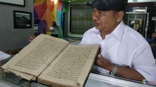 Pengelola Perpustakaan Sejarah dan Budaya Puspa Lulut, Lulut Edi Santoso, menunjukkan salah satu naskah kuno yang dipamerkan di Perpustakaan Umum Kota Malang. (Foto: Nurlayla Ratri/MalangTIMES)