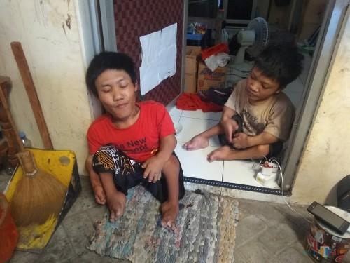 Hendra Kristianto (baju merah) bersama adiknya dirumah kost berukuran 3x3 meter. (eko Arif s /JatimTimes)