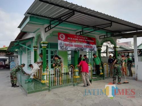 Anggota Koramil Wlingi dan masyarakat gotong royong bersihkan musala.