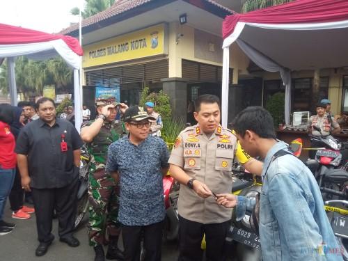 Kapolres Malang Kota, AKBP Dony Alexander saat menyerahkan kembali motor masyarakat yang sempat dicuri (Anggara Sudiongko/MalangTIMES)