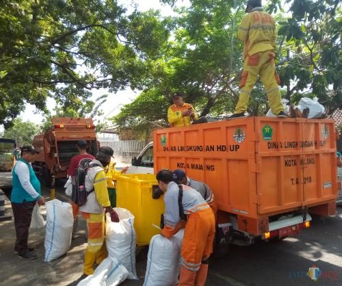 Proses pengakutan sampah ke atas truk yang dilakukan pasukan kuning DLH Kota Malang (Anggara Sudiongko/MalangTIMES)