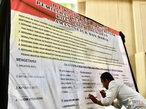 Salah satu calon kepala desa saat menandatangani deklarasi dama di Graha Pancasil, Balai Kota Among Tani, Senin (30/9/2019). (Foto: Irsya Richa/MalangTIMES)