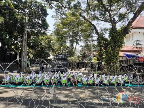 Pasukan Polwan Polres Makota saat melantunkan Asmaul Husna di tengah massa demonstrasi, Senin (30/9). (Arifina Cahyanti Firdausi/MalangTIMES)