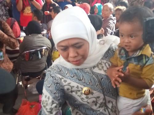 Gubernur Jatim Khofifah Indar Parawansa yang menujukkan kebahagiannya saat warganya bisa tiba dengan selamat, langsung menggendong erat salah seorang anak perantau (Anggara Sudiongko/MalangTIMES)