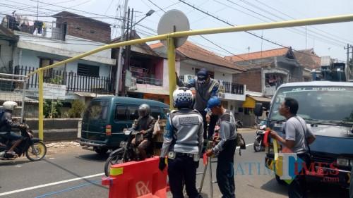 Petugas Dishub Kota Malang tengah menjaga dan memasang portal di area Jembatan Muharto (Pipit Anggraeni/MalangTIMES).