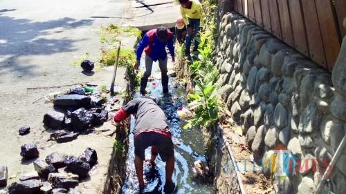 Petugas DPUPR Kota Batu saat mengangkat sampah yang ada dalam saluran drainase dan gorong di Jalan Panglima Sudirman sebelum musim hujan.
