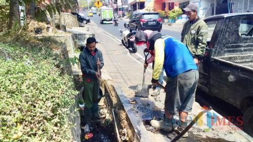 Petugas DPUPR Kota Batu saat mengangkat sampah yang ada di dalam saluran drainase dan gorong di Jalan Panglima Sudirman sebelum musim hujan.