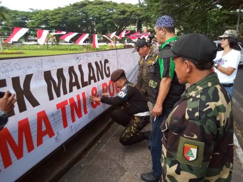 Banser saat ikut membubuhkan tanda tangan pada spanduk sebagai bentuk dukungan untuk menjaga konduaifitas dan keutuhan NKRI, serta melawan kelompok-kelompok yang ingin mengacau (Anggara Sudiongko/MalangTIMES)