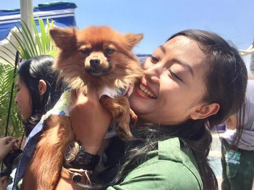Salah satu pengunjung saat berswafoto dengan salah satu anjing di world animal day di Jawa Timur Park 2, Minggu (6/10/2019). (Foto: Irsya Richa/MalangTIMES)