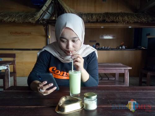 Pelanggan Coffee Times, Lisdya Shelly, sedang asyik bekerja sambil menikmati green tea Coffee Times. (Foto: Imarotul Izzah/MalangTIMES)