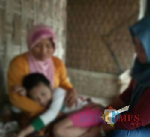 Mohammad Efendi, bocah yang menderita Retardasi mental sejak lahir dipangkuan ibunya. (Fahrurrosyi)