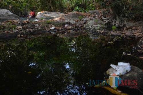Sejumlah warga Desa Marmoyo terlihat sedang memanfaatkan air di Sedang Tlimo untuk mencuci. (Foto : Adi Rosul / JombangTIMES)