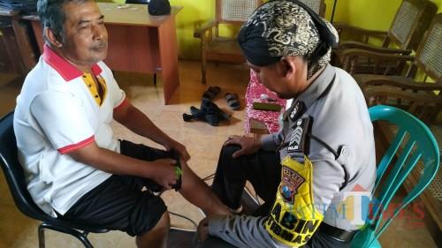 Bripka Agus Budiono saat mengobati salah satu pasien. (Eko Arif S /JatimTIMES)