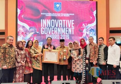 Kepala Balitbangda Kabupaten Malang M Hidayat (pegang piagam) bersama Bupati Malang Sanusi dan pejabat Kabupaten Malang (for MalangTimes)