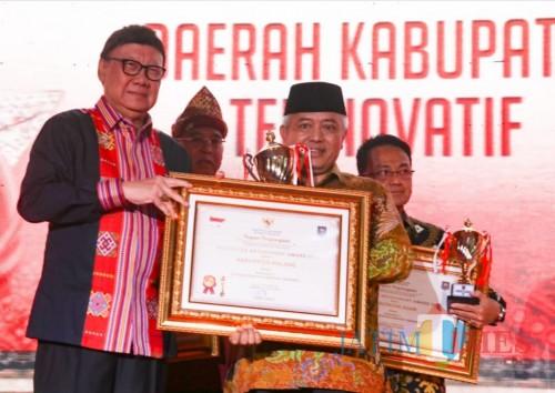Mendagri Tjahyo Kumolo (kiri) saat memberikan penghargaan Kabupaten Terinovatif kepada Bupati Malang Sanusi. (for MalangTimes)