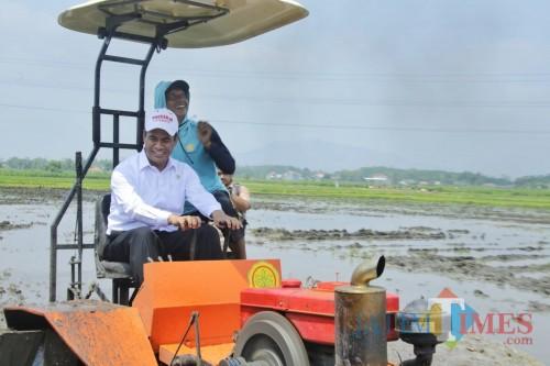 Menteri Pertanian Andi Amran Sulaiman saat mencoba alat pertanian canggih. (Eko Arif S / JatimTIMES)