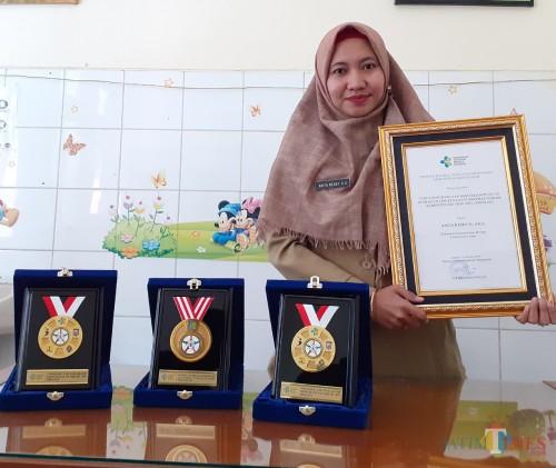 Sanitarian Pelaksana dari Puskesmas Polowijen Anita Resky DS saat menunjukkan penghargaan Sanitarian Terbaik (Arifina Cahyanti Firdausi/MalangTIMES)