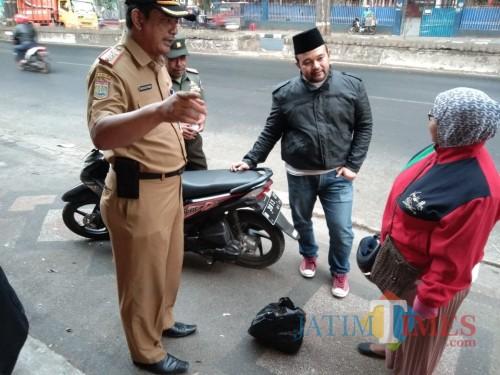 Bagus Sulistyawan Camat Singosari bersama tim saber sampah saat memberikan penjelasan kepada warga yang buang sampah sembarangan (Nana)