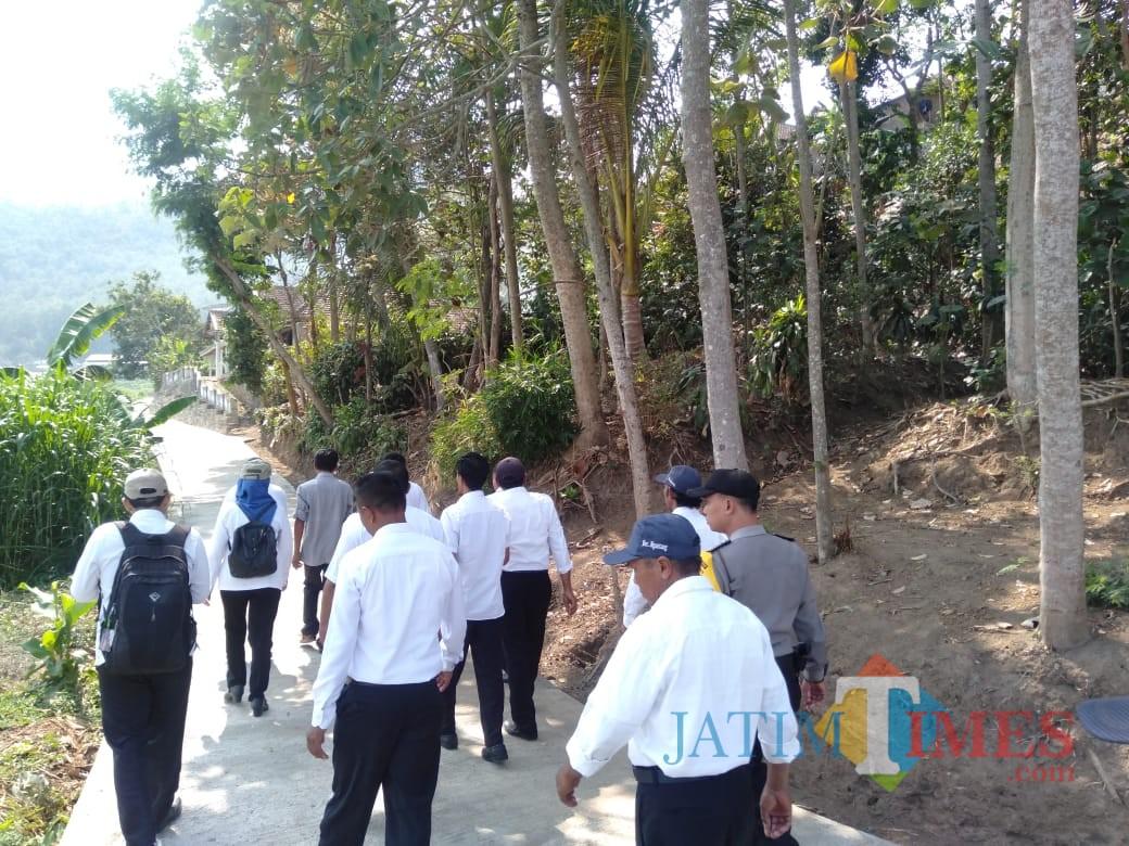 Disnaker Kabupaten Malang melihat hasil pembangunan rabat di Desa Mulyorejo, Ngantang, melalui skema padat karya infrastruktur (for MalangTimes)