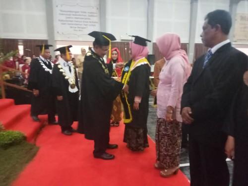 Rektor Unikama, Dr. Pieter Sahertian saat memasang slempang penghargaan sebagai wisudawan lulusan terbaik kepada empat mahasiswa (Anggara Sudiongko/MalangTIMES)
