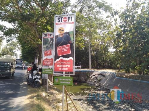 Poster bergambar foto warga yang tertangkap tangan membuang sampah di sungai terpajang di Jl Raya Tembelang, Jombang. (Foto : Adi Rosul / JombangTIMES)
