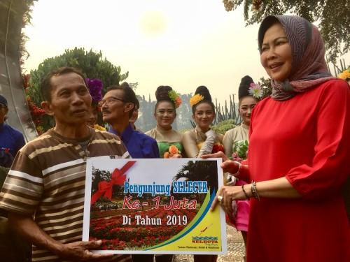 Wali Kota Batu Dewanti Rumpoko saat menyerahkan hadiah kepada pengunjung ke satu juta Iwanudin di Selecta, Minggu (20/10/2019). (Foto: Irsya Richa/MalangTIMES)